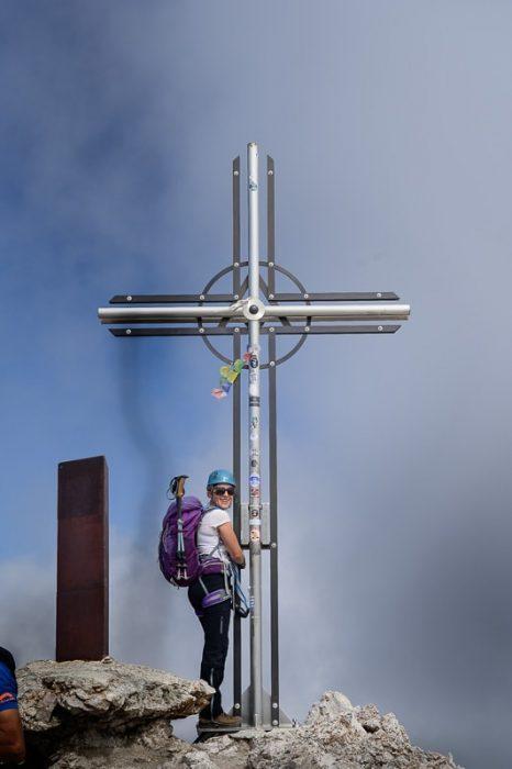 ženska ob križu na vrhu gore Sass Rigais