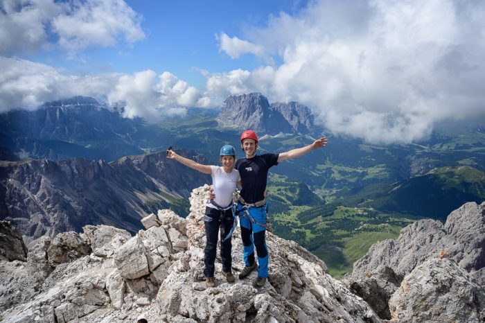 moški in ženska na vrhu gore v Dolomitih