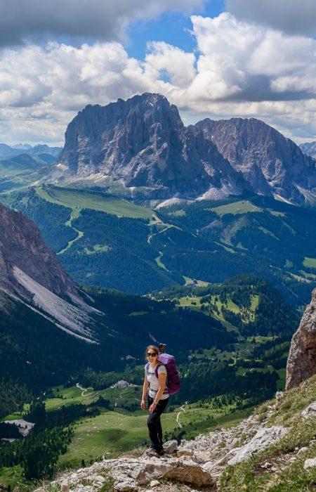 ženska z nahrbtnikom v gorah. v ozadju pogled na Sassolungo, Dolomiti