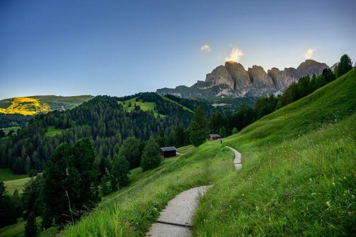 gorska pot med travniki in s pogledom na visoke gore v Dolomitih