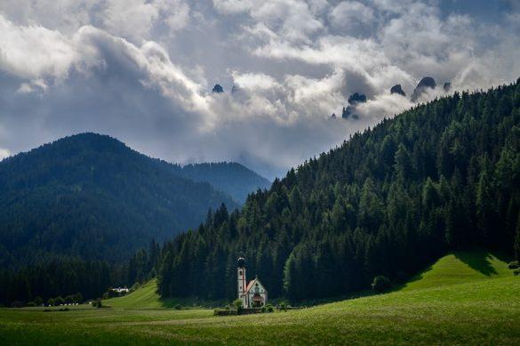 cerkev San Giovanni v Val di Funes. V ozadju gore v oblakih
