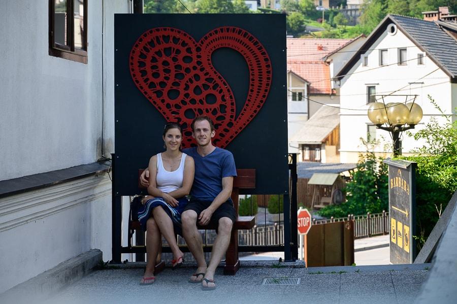moški in ženska na klopci pred znakom za Idrijo - čipkasto srce