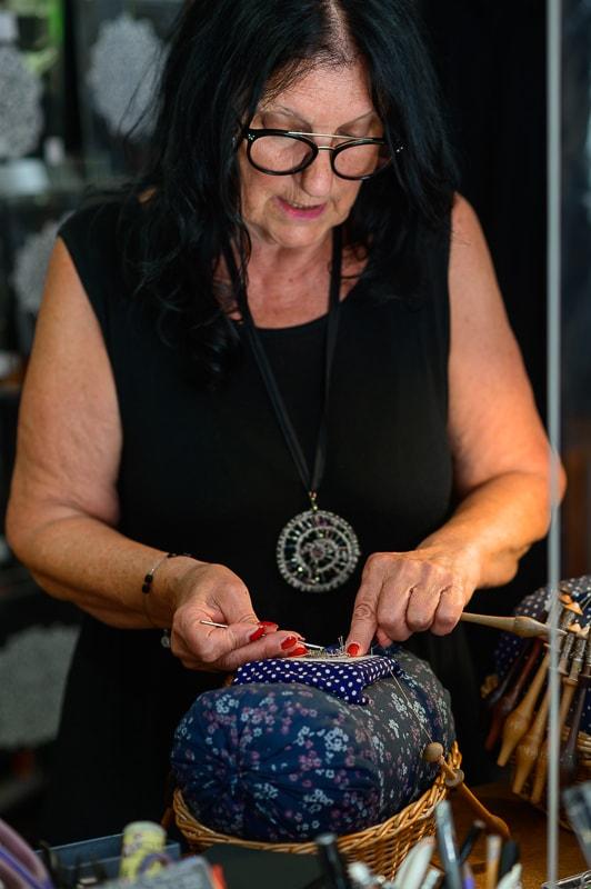 ženska v črni obleki in s črnimi lasmi dela idrijsko čipko - klekljanje