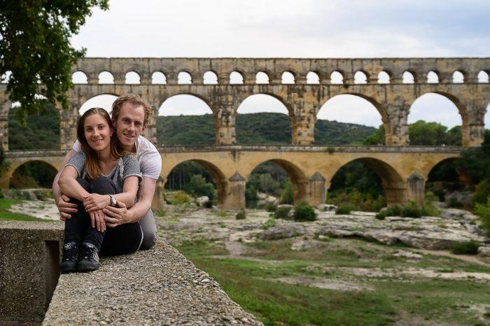 moški in ženska objeta sedita pred akvaduktom Pont du Gard