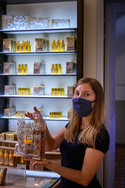 ženska z masko v trgovini s parfumi