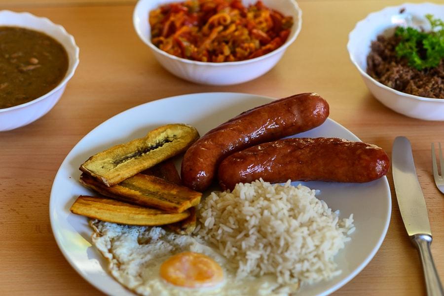 kolumbijska hrana: bandeja paisa. NA krožniku je pečena banana, klobasa, jajce in riž, v skodelicah pa omaka iz fižola, paradižnika in govedina