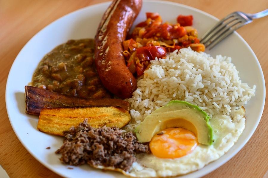 bandeja paisa, kolumbijska jed iz riža, avokada, fižola, klobase, banane, paradižnikove omake