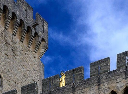 grajsko obzidje skozi katerega se vidi zlati kip marije