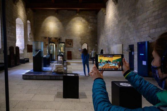 ženska drži v roki tablični računalnik s simulacijo nekdanje srednjeveške palače