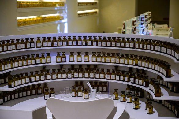 delovna miza mojstra parfumov. Miza s policami polnimi majhnih stekleničk