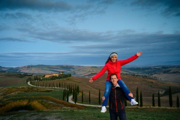 moški in ženska v toskani. cesta obdana s topoli v ozadju