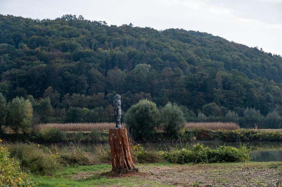 bronasti kip Melania Trump na lesenem podstavku sredi polja