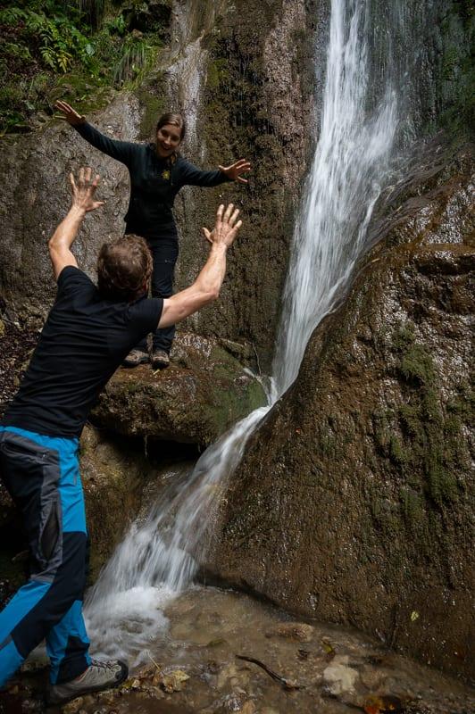 moški in ženska skačeta pred slapom