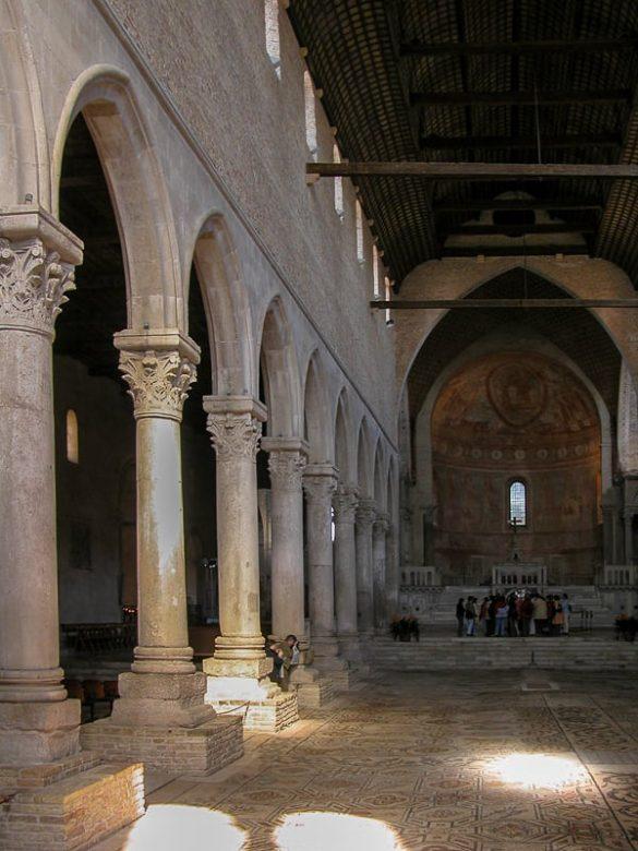 notranjost oglejske bazilike s stebri in talnim mozaikom