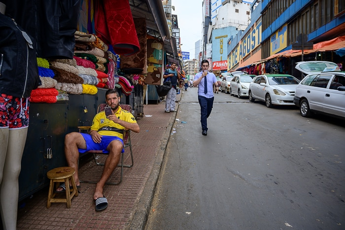 moški sedi pred stojnico z oblekami. Cuidad del Este