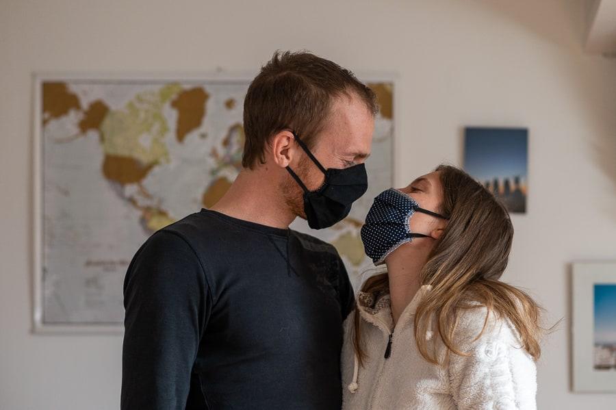 moški in ženska z masko na obrazu pred zemljevidom sveta