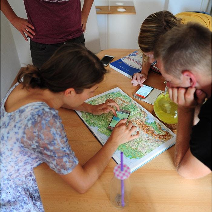 skupina mladih načrtuje potovanje ob zemljevidu