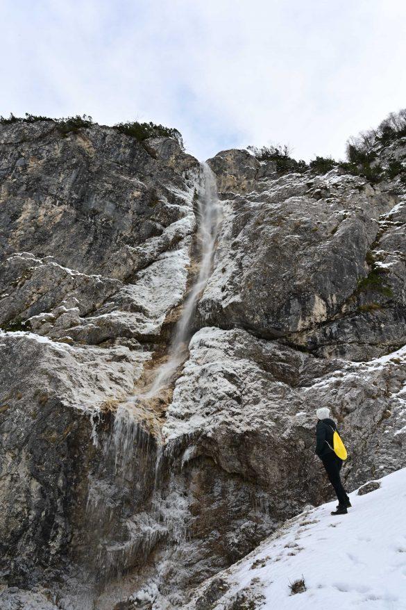 ženska z rumenim nahrbtnikom stoji pod deloma zmrznjenim slapom, dolina Tamar