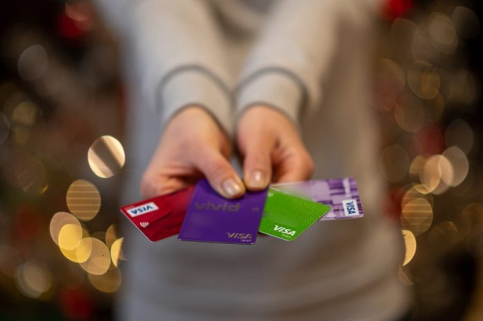 ženska drži v roki Visa kartice