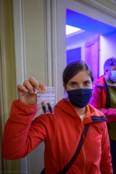 ženska z masko drži v roki epruveto z balzamičnim kisom