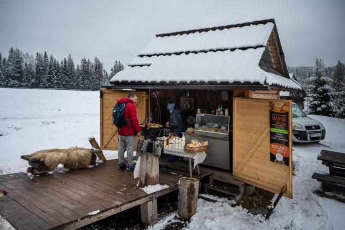lesena koča v zasneženi pokrajini, ki prodaja pečen sir