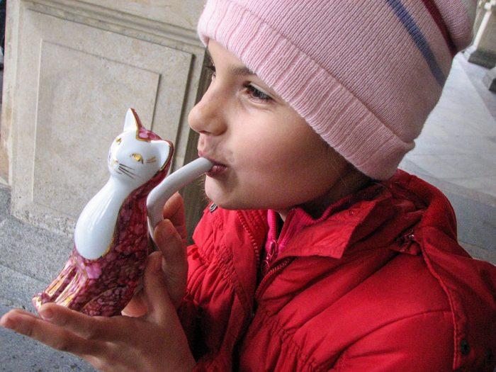 otrok pije iz skodelice v obliki mačke