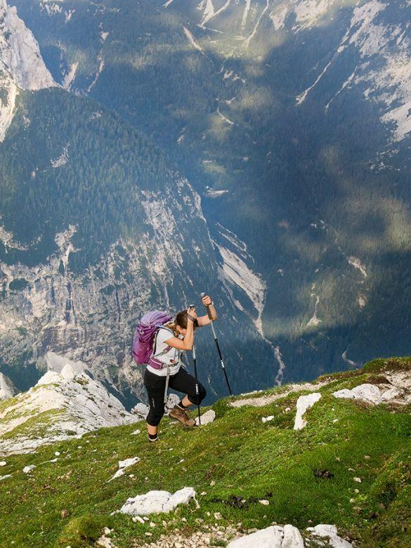 ženska si pomaga s pohodniškimi palicami pri hoji v gore