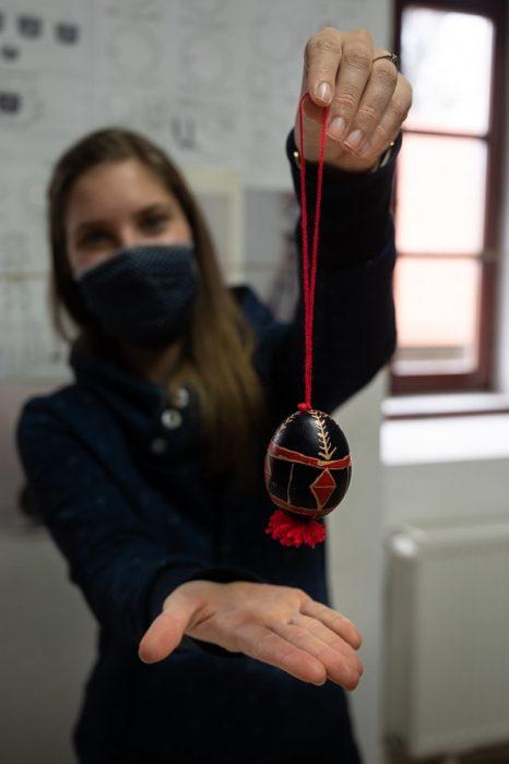 belokranjska pisanica, ki visi na nitki. Ženska drži belokranjsko pisanico na nitki