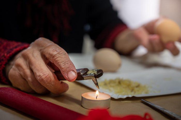 ženska drži pisač nad svečko