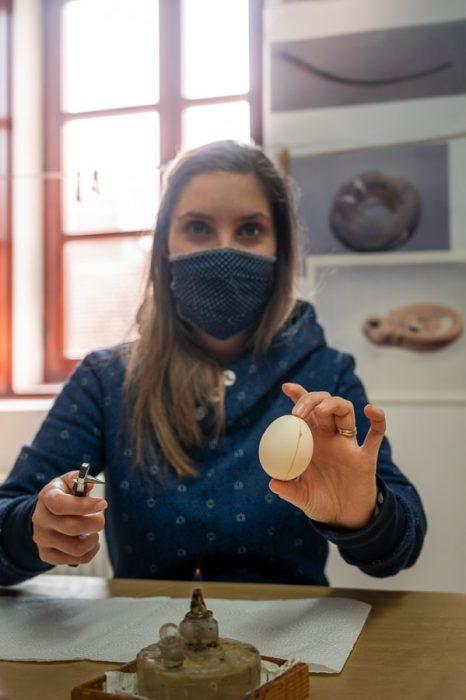 ženska z masko krasi velikonočno jajce