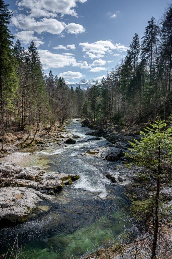 reka Mostnica in zasnežene bohinjske gore v ozadju