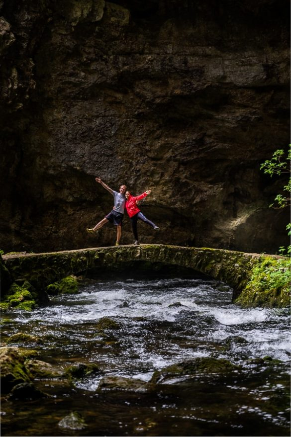 moški in ženska na kamnitem mostu nad reko