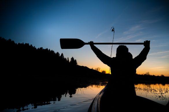 obris ženske v čolnu in z veslom v roki