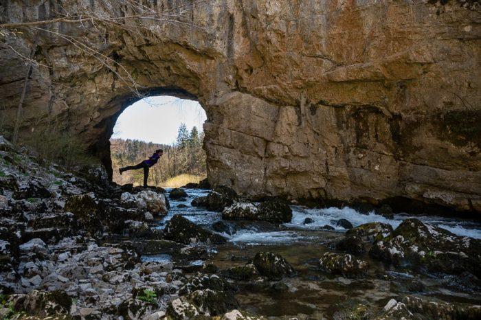 ženska pred naravnim tunelom v skali. Veliki naravni most, Rakov škocjan