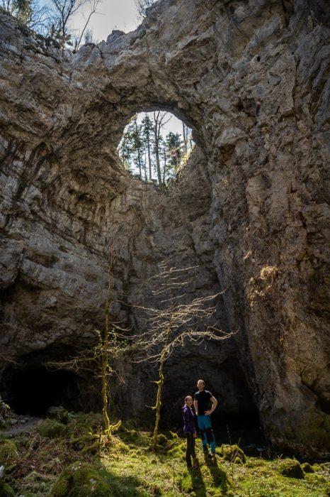 moški in ženska stojita pod Malim naravnim mostov, Rakov Škocjan