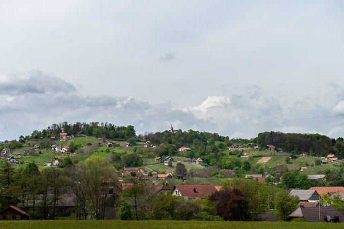 Dolenjska: pokrajina, griči, cerkev na vrhu hriba, zidanice in vinograd
