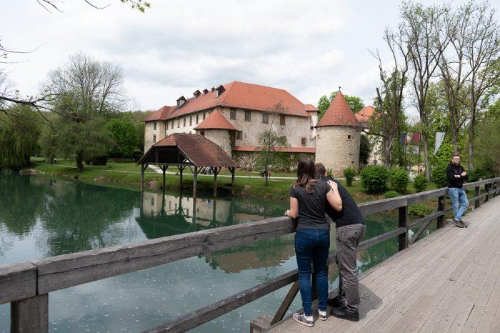 moški in ženska stojita na mostu pred gradom - grad Otočec