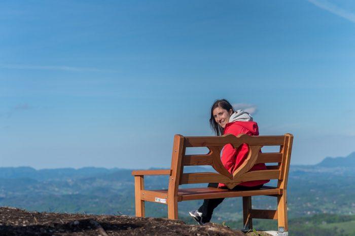 ženska sedi na klopci ljubezni z razgledom na hribovito pokrajino Kozjansko