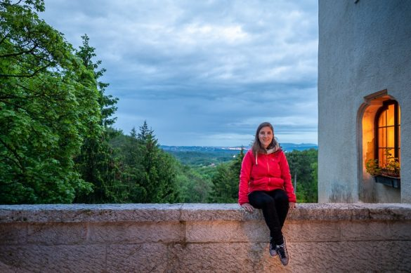 ženska sedi na kamniti ograji, grad Pišece