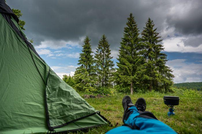 moški leži ob šotoru