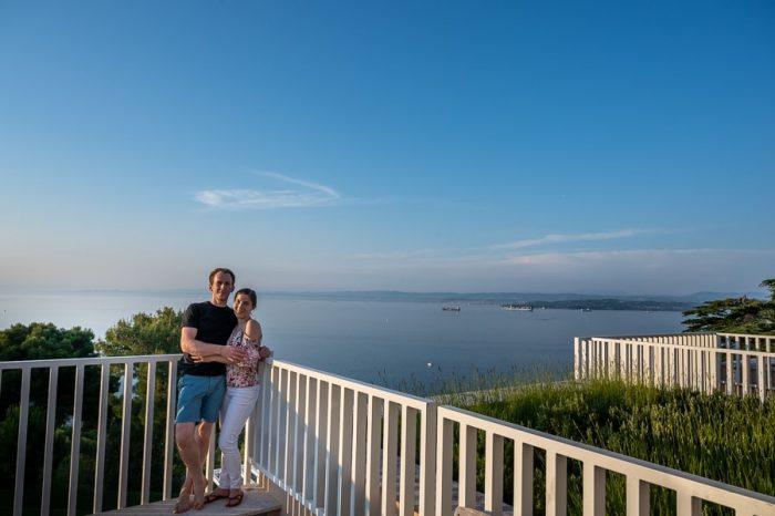 moški in ženska na terasi nad morjem