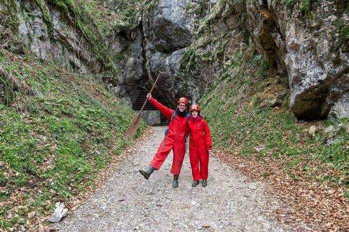 moški in ženska v rdečih jamarskih kombinezonih pred vhodom v Križno jamo