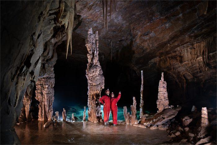 ženska in moški v rdečih jamarskih kombinezonih. križna jama