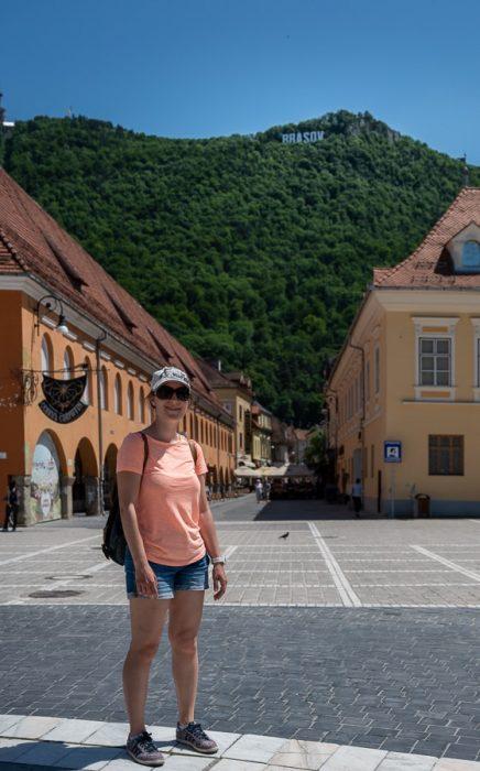 ženska na glavnem trgu v mestu Brasov. v ozadju gora z napisom BRASOV. Romunija