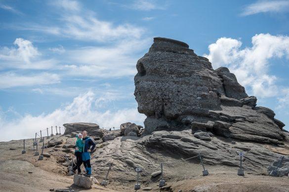 moški in ženska pred Sfingo - kamnito strukturo, Bucegi, Romunija
