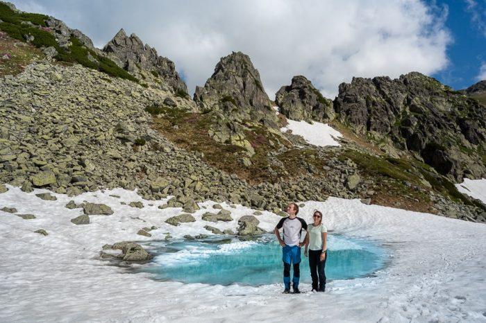 moški in ženska pri ledeniškem jezeru. nacionalni park Retezat, Romunija treking