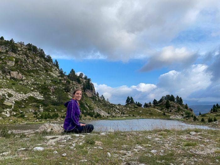 ženska sedi ob jezeru v Pirenejih. Andora. Žensko solo potovanje