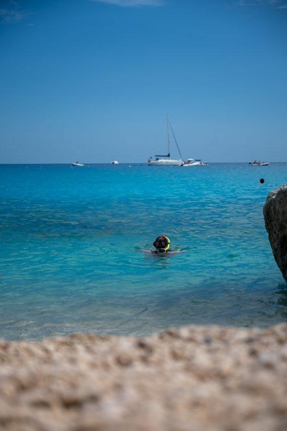 ženska v turkizno čisti vodi na plaži Cala Goloritze