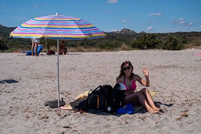 ženska pod senčnikom na beli mivkasti plaži, Sardinija