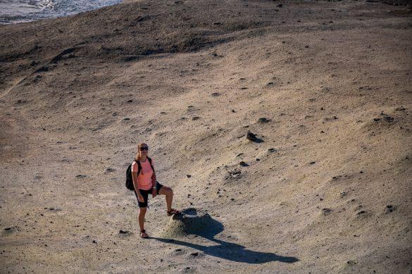 ženska na plaži Cane Malu stoji ob mini vulkančku